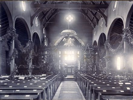 View of the interior of the first St Matthew's Church, c1900. The church is decorated with swags of greenery, suggestive of Christmas decorations